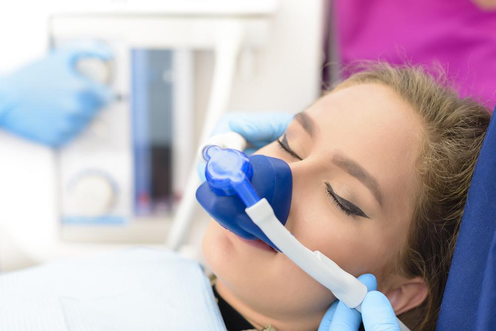 Beautiful woman getting inhalation sedation at dental clinic