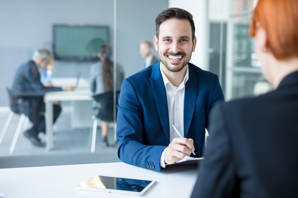 Man smiling showing his white teeth on a business meeting